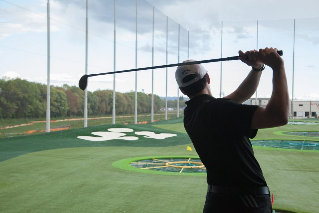 Golfer taking a swing at Topgolf in Tualatin Valley