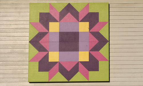 Block: Friendship Star (variation)  Established in 1923, the Laurel Home Club is still used for community events. This Friendship Star block, with its vibrant colors, was chosen to celebrate the closeness of the community and the many friendships that came from gathering there.